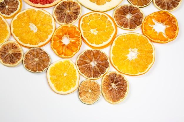 Fatias secas de várias frutas cítricas em fundo branco