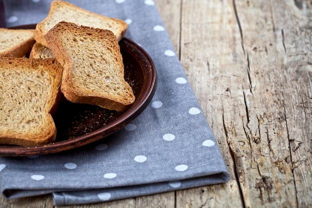 Fatias torradas do pão do cereal no close up cerâmico marrom da placa no guardanapo de linho no fundo de madeira rústico da tabela.