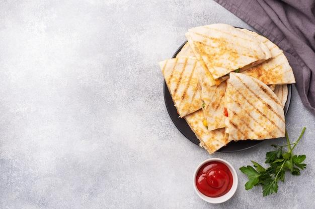 Fatias triangulares de uma quesadilla mexicana com molho.