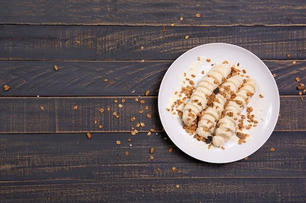 Fatie banana com granola em uma mesa de madeira