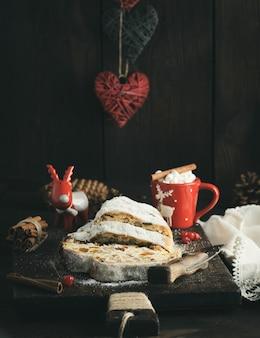 Fatie o tradicional bolo europeu stollen com nozes e frutas cristalizadas polvilhadas com açúcar de confeiteiro, close-up
