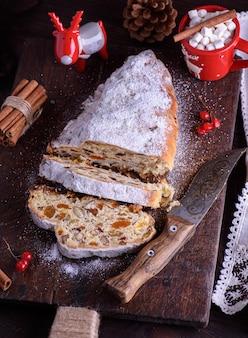 Fatie o tradicional bolo europeu stollen com nozes e frutas cristalizadas polvilhadas com açúcar de confeiteiro, vista de cima