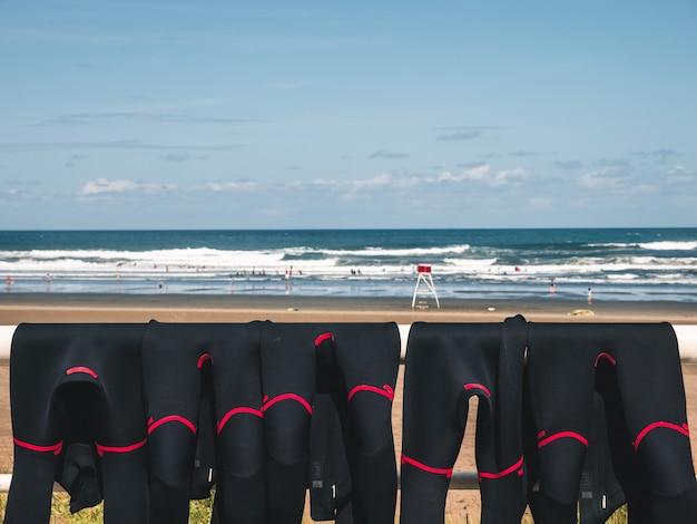 Fatos de neoprene secando ao sol em uma grade, pessoas desfrutando de um lindo dia na praia