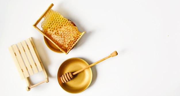Favo de mel amarelo quebrado com mel na mesa ao lado de trenós decorativos