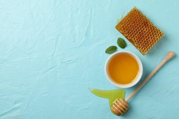 Favo de mel, concha e tigela com mel no fundo azul