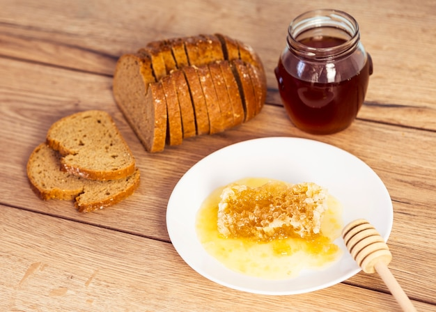 Favo de mel doce; pote de mel e pão sobre a mesa