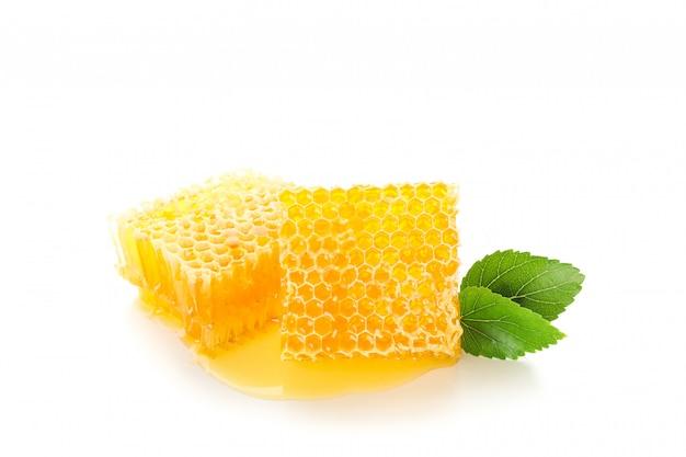 Favo de mel e folhas isoladas no branco
