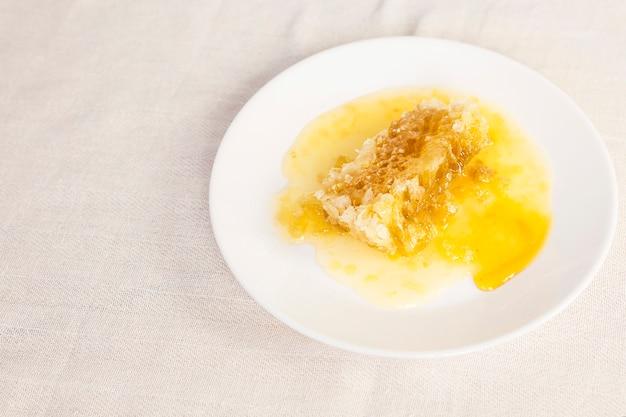 Favo de mel fresco na placa cerâmica branca sobre o pano de tabela