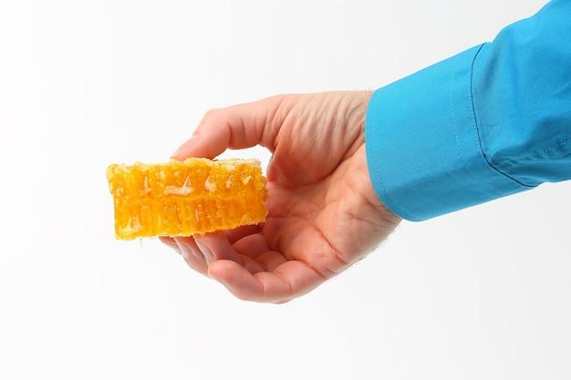 Favo de mel na mão em fundo branco