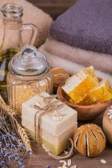 Favo de mel, óleo cosmético, sal marinho, aveia e sabonete artesanal com mel em fundo de madeira rústico. ingredientes naturais para máscara facial e corporal ou esfoliante caseiros. cuidados com a pele saudável. conceito de spa.