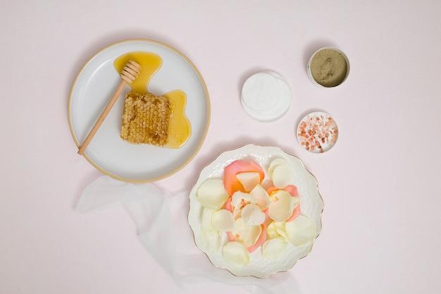 Favo de mel; pétalas; almofada de algodão; barro de rhassoul; sal de rocha e ervas à terra no fundo branco