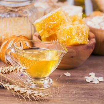 Favo de mel, sal marinho, aveia e sabonete artesanal com mel em fundo de madeira rústico. ingredientes naturais para máscara facial e corporal ou esfoliante caseiros. cuidados com a pele saudável. conceito de spa.