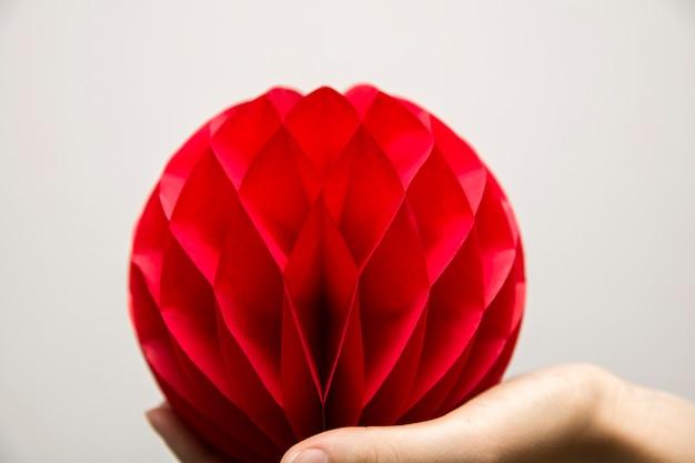 Favo de mel vermelho pom-pom papel bola decoração na mão humana