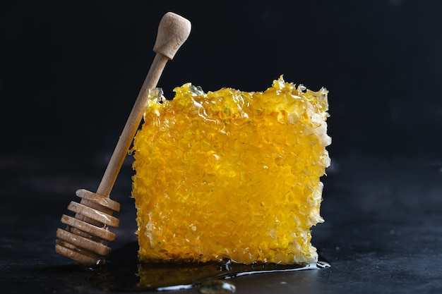 Favos de mel com mel fresco e colher de mel em fundo escuro. fechar-se