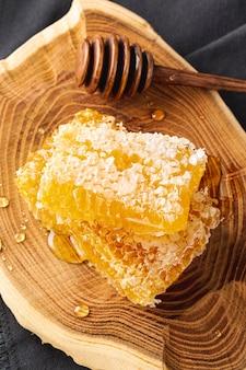 Favos de mel de alto ângulo com dipper na bandeja de madeira