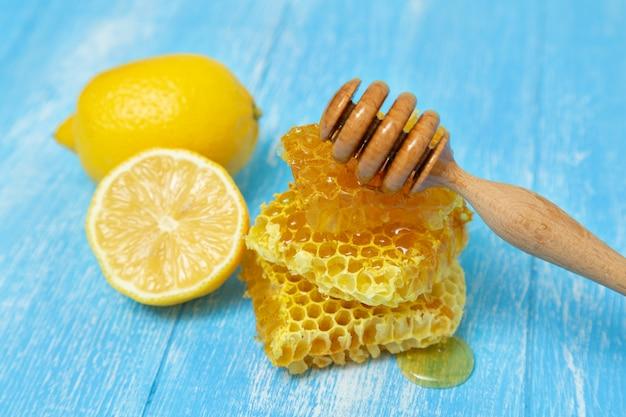 Favos de mel e limão mentem sobre um azul de madeira.