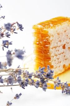 Favos de mel em uma tigela de vidro e ramos de lavanda em cima da mesa.