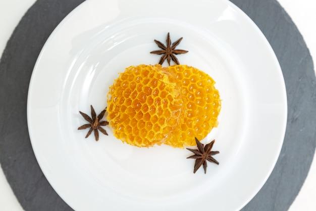 Favos de mel redondos mentem em um prato em um branco de madeira.