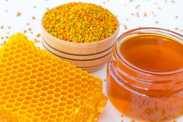 Favos de mel, um pote de mel escuro e pólen.