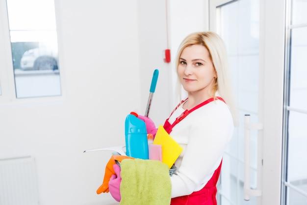Faxineira com um balde e produtos de limpeza no fundo do escritório.