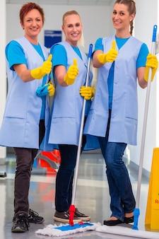 Faxineiras trabalhando em equipe mostrando o sinal de positivo