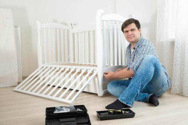 Faz-tudo montando móveis de madeira em quarto de criança