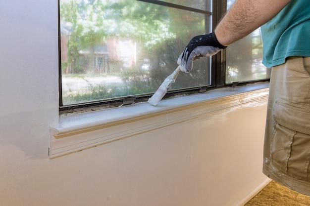 Faz-tudo pinta uma moldura de janela na reforma de uma casa
