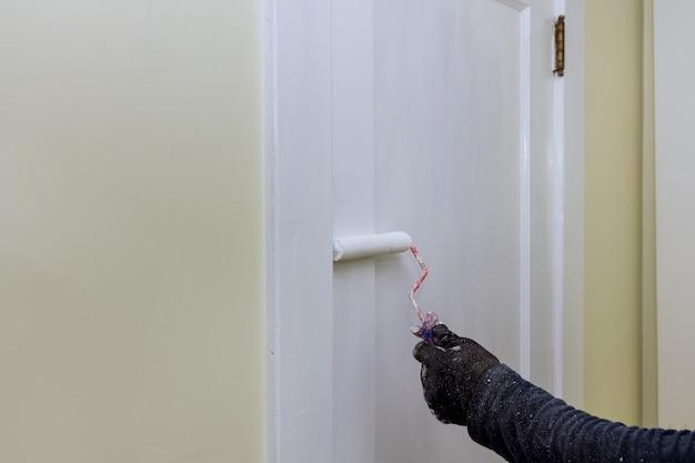 Faz-tudo, pintor de renovação doméstica de acabamento de portas usando pintura a rolo à mão com luvas