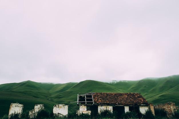Fazenda abandonada em prados verdes nas montanhas