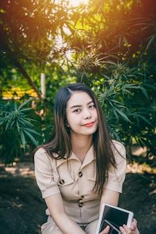 Fazenda de cannabis do proprietário da empresa mulher, menina adolescente com maconha ou planta erval de cânhamo verde sorriso feliz.