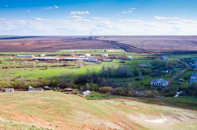 Fazenda de gado da aldeia e uma plataforma de perfuração no campo