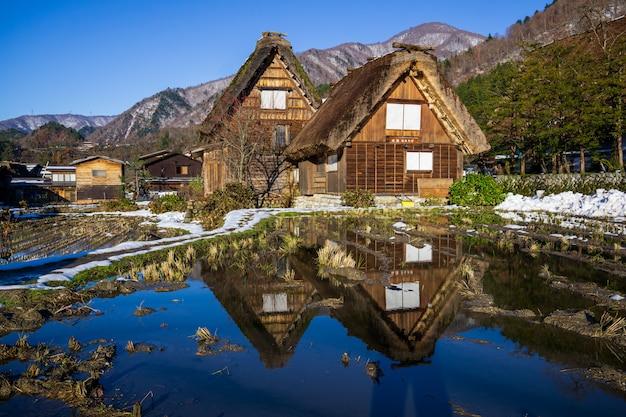 Fazenda de madeira de herança com reflexo de água na famosa vila do japão.
