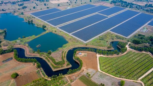 Fazenda de painéis solares entre campos agrícolas em vista aérea. na tailândia