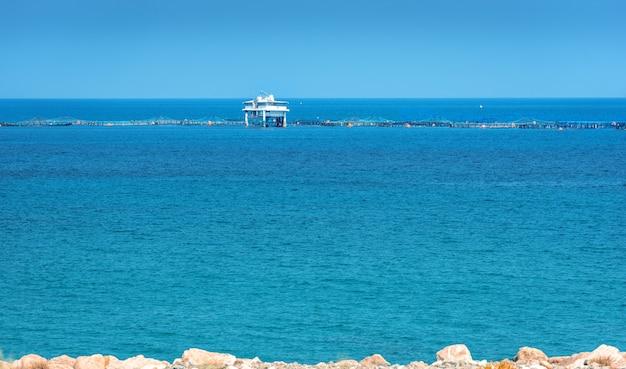 Fazenda de peixes crescendo robalo e peixe dourado vista da costa no porto de limassol