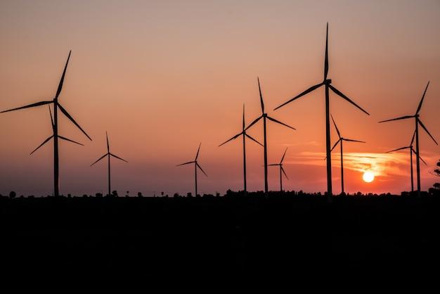 Fazenda de turbina de vento e campos agrícolas com raios de luz ao pôr do sol