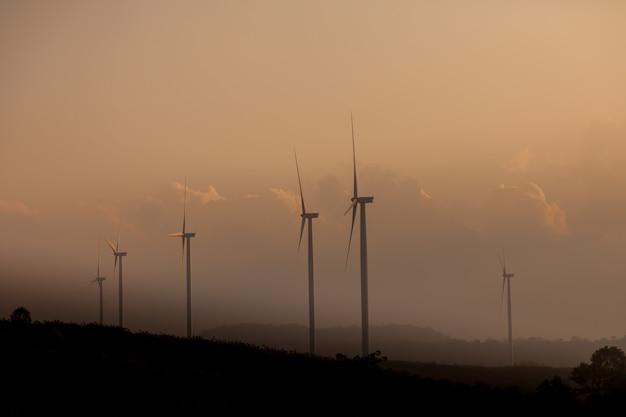 Fazenda de turbinas eólicas de silhueta ao pôr do sol.