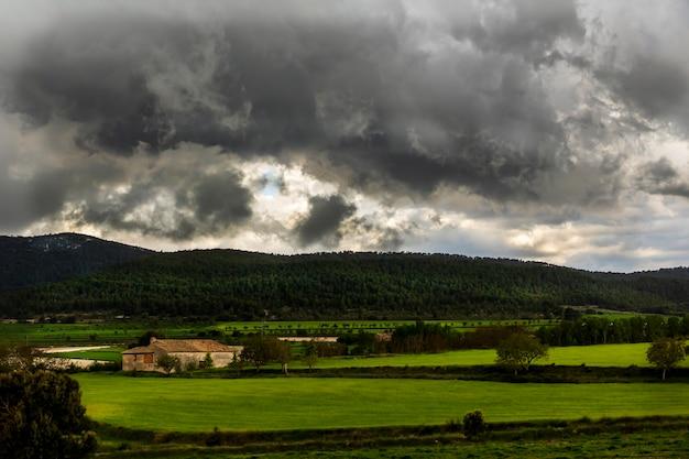 Fazenda em um prado verde em um dia com nuvens brancas e cinza e raios de sol com montanhas ao fundo.