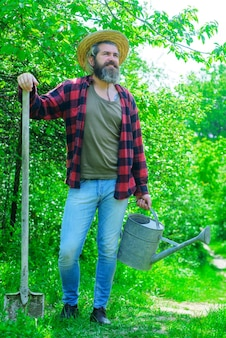 Fazenda. homem feliz com regador e pá.