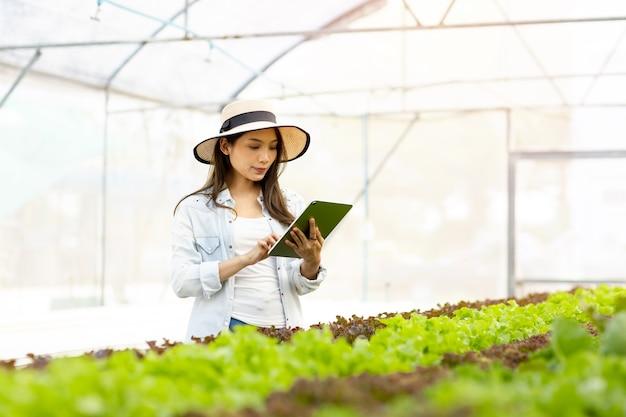 Fazenda inteligente e conceito de tecnologia de fazenda. jovem agricultor asiático inteligente usando tablet para verificar a qualidade e a quantidade de horta hidropônica orgânica em estufa.