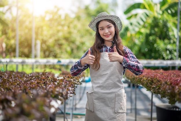 Fazenda vegetal hidropônica. jovem mulher asiática mostrando o polegar para cima de sua fazenda de hidroponia