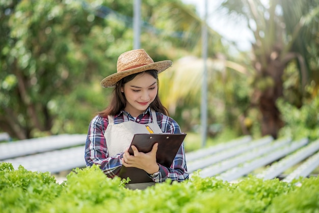 Fazenda vegetal hidropônica. mulher asiática sorridente estudando, examinando e pesquisando vegetais em uma fazenda hidropônica