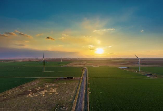 Fazendas de turbinas eólicas no pôr do sol colorido mostrando obras de energia renovável, energia eólica sopra no oeste do texas