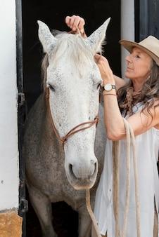 Fazendeira com seu cavalo no rancho