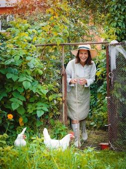 Fazendeira com um pedaço de pau está soltando galinhas caipiras do galinheiro na grama verde.