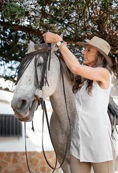 Fazendeira equipando seu cavalo no rancho
