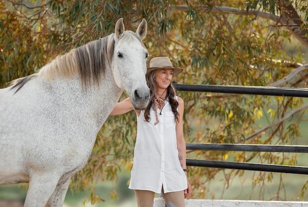 Fazendeira sorridente acariciando seu cavalo