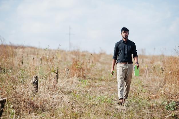 Fazendeiro asiático do engenheiro agrônomo sul com a prancheta que inspeciona árvores cortadas no jardim da exploração agrícola. conceito de produção agrícola.