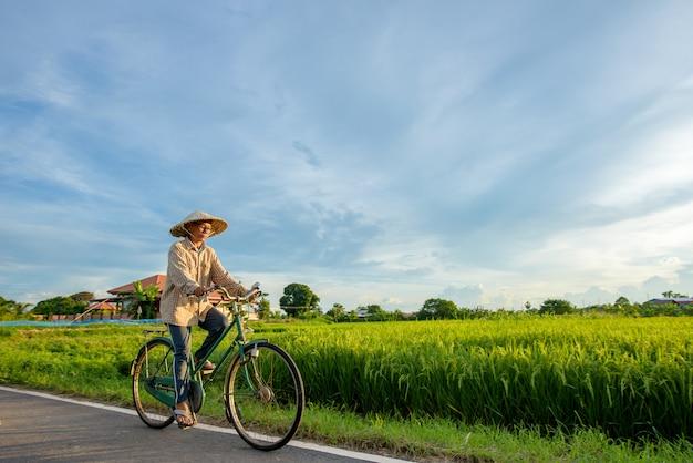 Fazendeiro asiático idoso andando de bicicleta