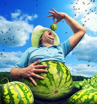 Fazendeiro bizarro com melancia em vez do abdômen no campo no verão