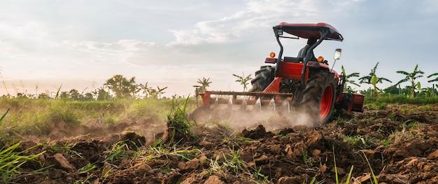 Fazendeiro com trator prepara o terreno para o cultivo agrícola.